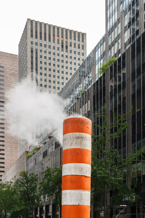 wafting: Steam rising out of a subway vent in a street of New York City Stock Photo