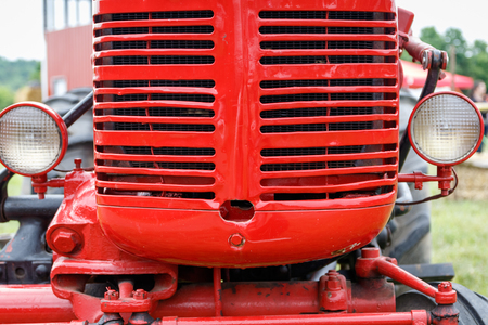 grille: Close-up of the grille of a shiny red tractor