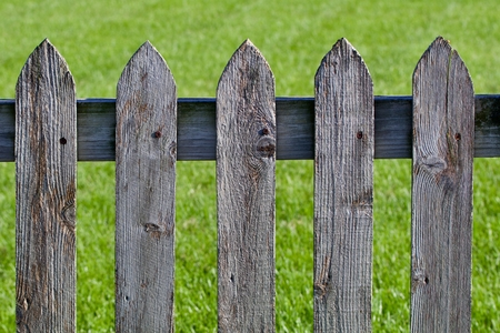 Weathered wood picket fence against the grass