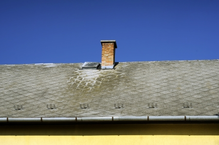 Chimneys on roof of red tiles with blue sky and clouds