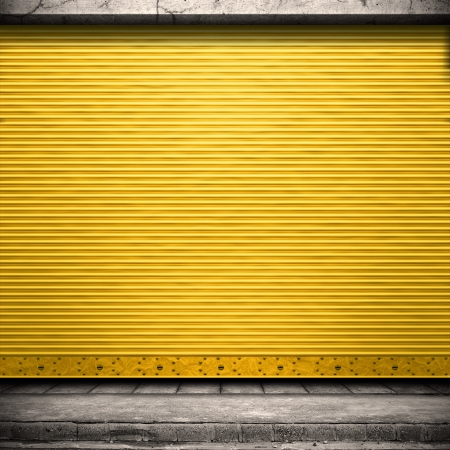 shutter door: Painted corrugated metal door with conrete wall and ground.  Stock Photo