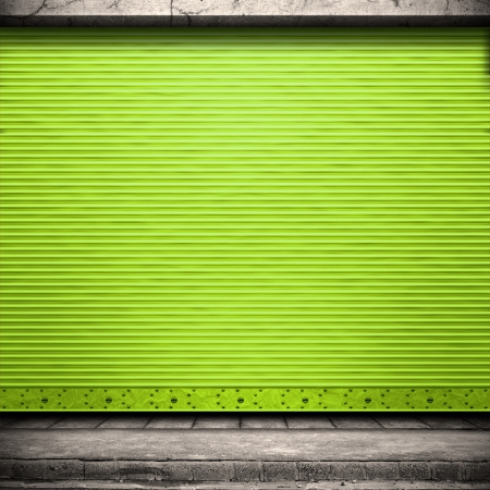 Painted corrugated metal door with conrete wall and ground.  Stock Photo