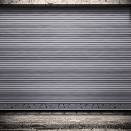 corrugated iron: Painted corrugated metal door with conrete wall and ground.  Stock Photo