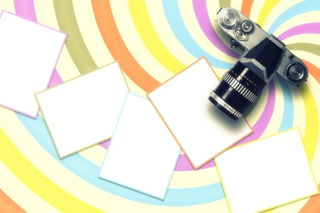 Blank card and vintage camera on colored spiral line background