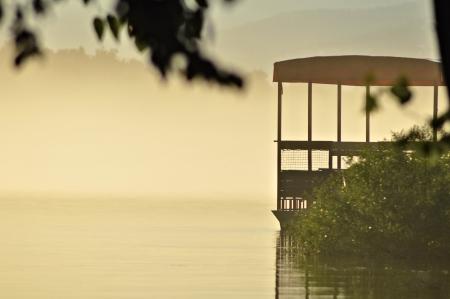 puesta de sol sobre el r�o en la niebla de la pizca del barco