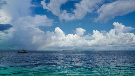 Light rainbow over the ocean, horizon seafront, blue sky and cloudscape.