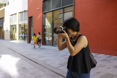 Shenzhen, China, November, 2018. The girl is taking photos on the street at UpperHills. UpperHills is a top-class urban complex composed of multi-shopping space, dining, leisure, and accommodation. 新聞圖片