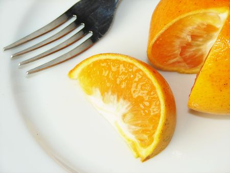 Citrus on a white plate with fork Banco de Imagens