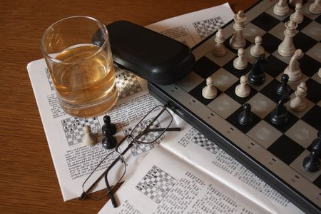 A glass of whisky and an open book and chess.