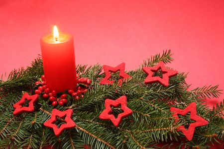 Christmas candle and decorations on a red background. photo