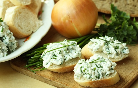 Baguette slices with spread from chives on cutting board  Stock Photo
