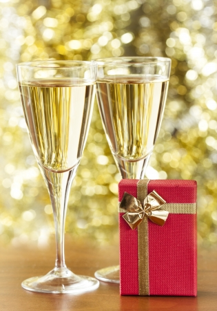 Two glasses of champagne and gold background