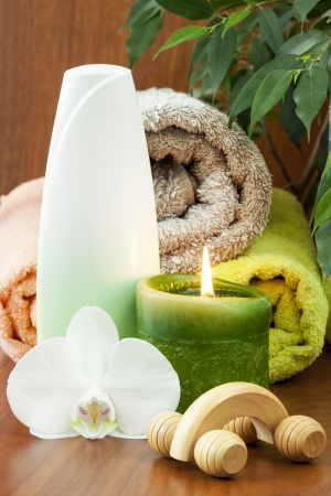 Bottle of massage cream and candle