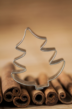 Cinnamon and christmas baking cutter on a brown background