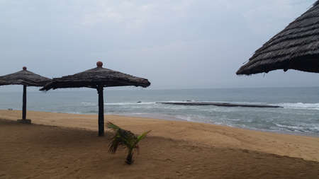 A view of a reef from a Beach Resort in Togo. Empty cabanas and palm trees on a clean beach in the city of Lome, Togo