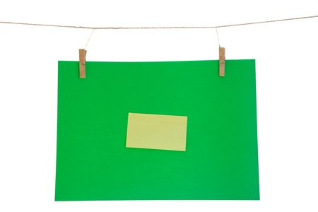 green paper sheet and yellow on a clothes line. Isolated on white background.  photo