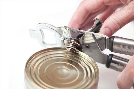 hand Tin opener opening a can of food isolated on white