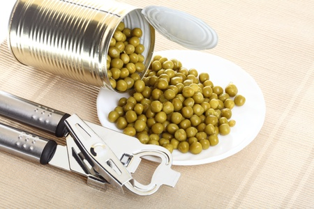 cooking implement: Tin opener opening a can of food canned, tinned peas