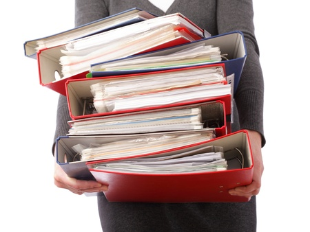 document management: vrouw in grijs met stack van mappen stapel met oude documenten en rekeningen. Geïsoleerd op witte achtergrond Stockfoto