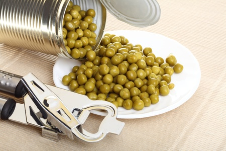 Tin opener opening a can of food canned, tinned peas