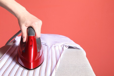household chores - red iron in hand and white shirt   photo