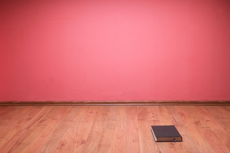 book to lie in floor red wall background Stock Photo