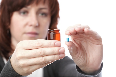 woman with pill - blue white pills in woman hand isolated  photo