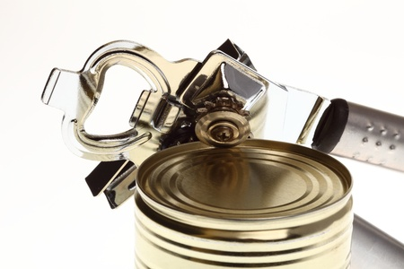cooking implement: Tin opener opening a can of food isolated on white