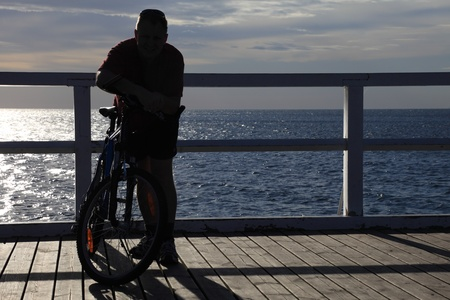 mountainbiking: silhouette of a man bike at the pier, jetty in morning sea