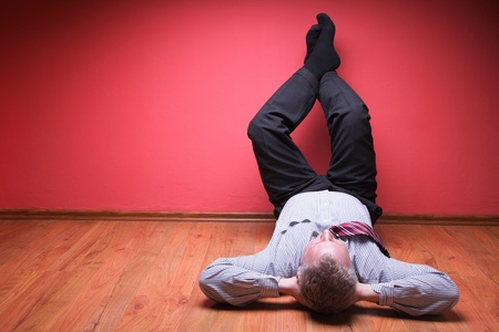 men lying in the floor on red wall background Stock Photo