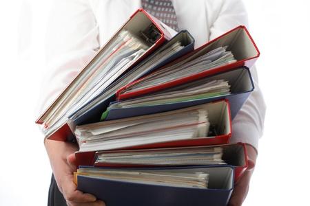 gestion documental: pila de hombre que sostiene la pila de carpetas con documentos antiguos y las facturas. Aisladas sobre fondo blanco