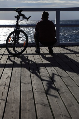 mountainbiking: man bike at the pier, jetty in morning sea