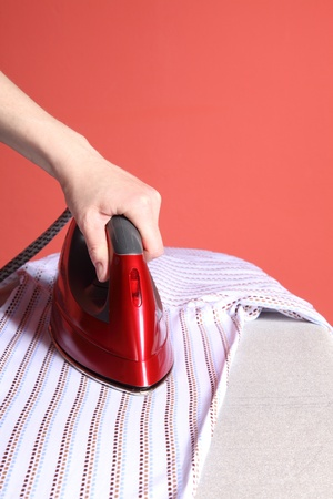 household chores - red iron in hand and white shirt   Stock Photo