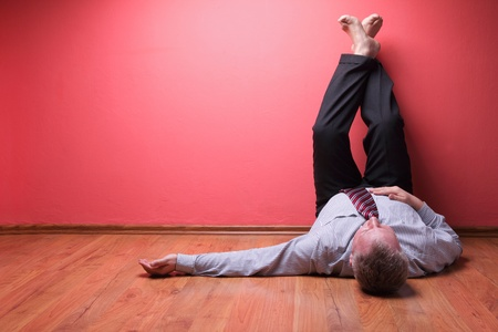 lying on the floor: men lying in the floor on red wall background Stock Photo