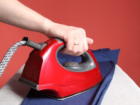 household chores - red iron in hand and navy blue shirt   photo