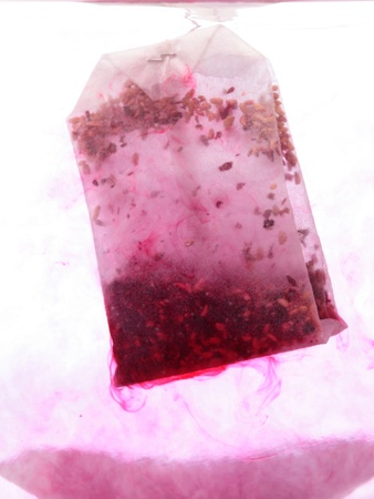 red Teabag in hot water in white background Stock Photo - 11941760