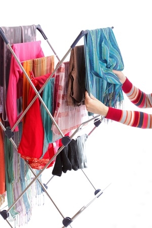 dry fruits: colorful clothes hanged for drying after laundry clothes airer, clothes dryer isolated on white and woman hand