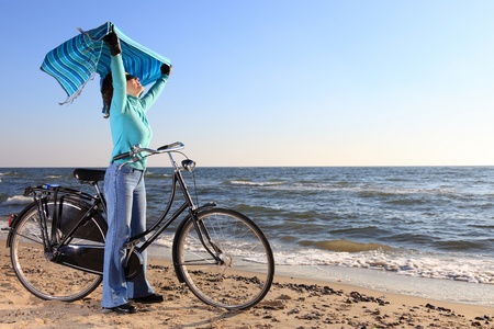 woman in blue, bike and shawl at sea shore photo