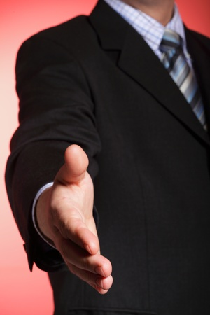 business man open hand ready to seal a deal red background photo