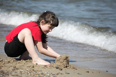 Little girl playing on beach outdoor Stock Photo