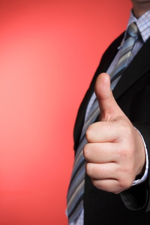 Business man showing thumb up - selective focus on hand photo