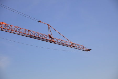 Construction crane against the blue sky photo