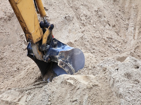 bucket digger of an earthmover on sand background photo