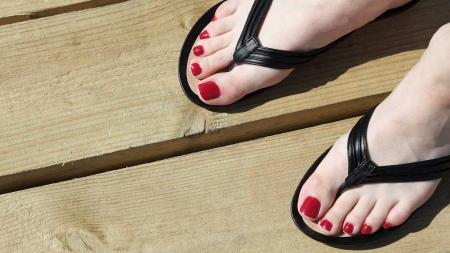 sandalias: Pies femeninos con flip-flops al aire libre del clavo rojo Foto de archivo