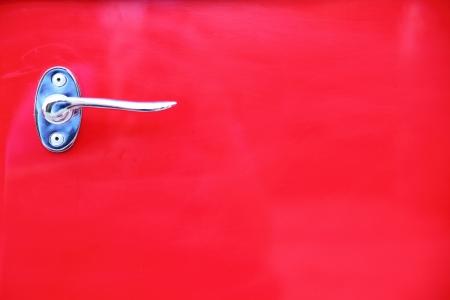 detail of vintage red car door photo