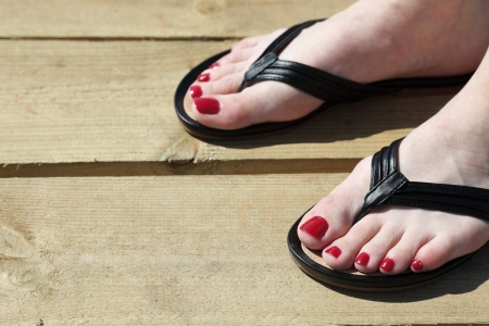 long toes: Female feet with flip-flops outdoor red nail