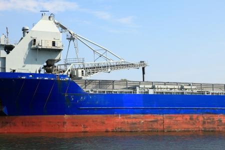 cranes in a port loading a ship coal