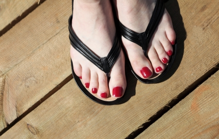 Female feet with flip-flops outdoor red nail