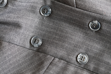 Close detail of a button on a pin striped business suit
