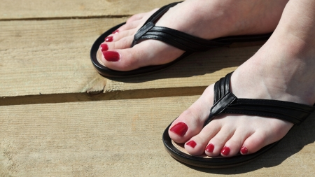Female feet with flip-flops outdoor red nail photo